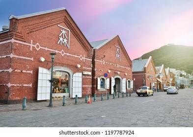 HAKODATE, JAPAN - October 22, 2014: Historic red brick warehouses and Mount Hakodate at sunset on Hakodate Mountain in Hakodate, Hokkaido, Japan.