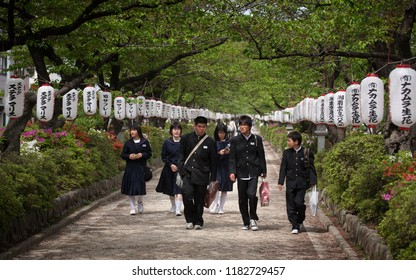 HAKONE,  JAPAN - APRIL 18 2009: Group of Japanese school children walking in a park with lampions