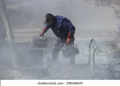 Hakone, Japan - April 9, 2015: Unidentified man is boiling black eggs believed to help extend 7 years of life if eating one at Owakudani, a volcanic valley with active sulphur vents and hot springs.
