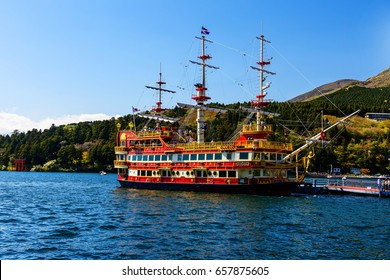 HAKONE, JAPAN - MAY 5, 2017: Red pirate ship at dock and Torii gate Hakone shrine at Ashi lake. Pirate tourist ship is one of the most famous Hakone signs.