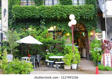 HAKONE,  KANAGAWA, JAPAN - June 15, 2018. Romantic restaurant with overgrown ivy walls, plants, blooming Hydrangea flowers, Japanese menu board and outdoor terrace with parasol and furniture.