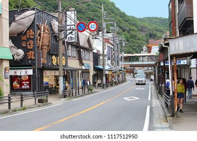 HAKONE, KANAGAWA, JAPAN - June 15, 2018. People are shopping and walking in the main street with restaurants, three dimensional seafood signs, shops and stores and green mountains at the background.