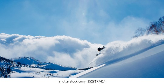 "Hakuba Valley, Tsugaike / Japan - February 2019: Sunny ""blue bird"" backcountry skiing after famous Japanese powder dump, ""Japow"". Deep untouched snow off pist."