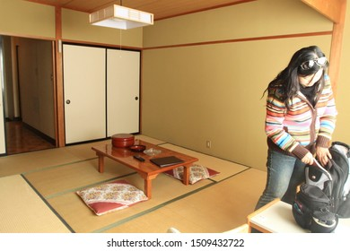 Hakuba/Japan - November 27th, 2009: Low table and sitting cushions with tatami floor in traditional Japanese style hotel room with a female guest on the right side