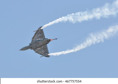 HAL Tejas of Indian Air Force performing aerobatic maneuver with smoke trails.