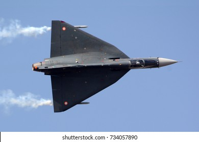 HAL Tejas performing aerobatic maneuver with smoke trails.