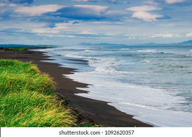 Halaktyr beach. Kamchatka. Russian federation. Dark almost black color sand beach of Pacific ocean. Stone mountains and yellow grass are on a background. Light blue sky.