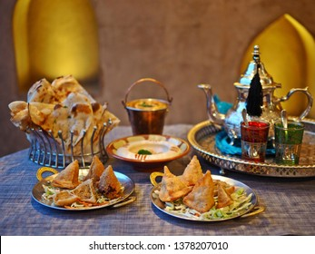 Halal chicken samosas served with vegetable on the dining table with blurred dal makhani, hummus, naan bread, tea pot. Ramadan dish cooked with blessing meat, food preparation for the iftar meal.