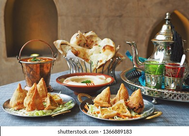 Halal chicken samosas and vegetable samosas with blurred dal makhani, hummus, naan bread, tea pot on the dining table. Ramadan food preparation for iftar meal during the holy month. (selective focus)