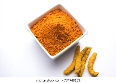 Haldi / Turmeric powder in ceramic bowl with whole dried Sticks over plain background