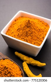Haldi OR Turmeric powder in ceramic bowl with whole dried Sticks over plain background