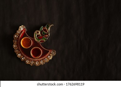 Haldi-Kumkum container in peacock design diya containing natural color powders that are used while worshipping God and on at auspicious occasions by Hindus isolated on black background. Copy space.