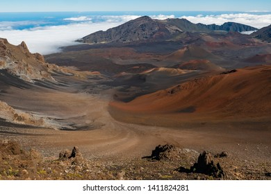 Haleakala Crater landscape photo with clouds during the daytime.