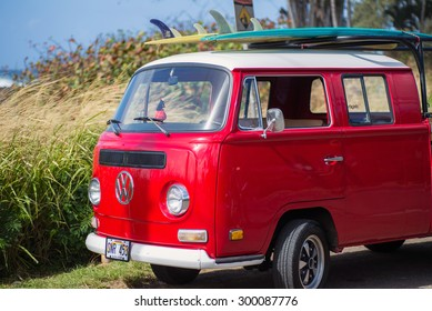 HALEIWA, HAWAII - FEB 10:  Classic red volkswagon van with surfboards on rack on top on sunny day in Haleiwa, Hawaii on February 10, 2015.  Haleiwa is known for its big waves in the winter season.