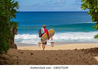 Haleiwa, Hawaii / USA - Jan. 1, 2018: A Surfer heading to the beach to surf some waves