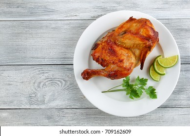 half of appetizing grilled chicken with golden brown crust  with lime slices and parsley on white plate, on wooden table, view from above