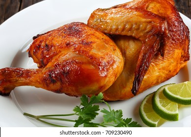 half of appetizing grilled juicy chicken with golden brown crust with lime slices and parsley on white plate, on wooden table, horizontal view from above, close-up, macro