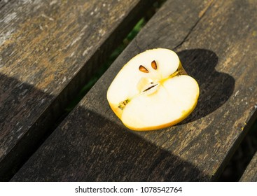 Half of an apple on a wooden bench