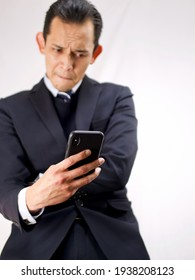 Half Asian (Filipino) Caucasian (Swedish) businessman in dark professional suit holding black smartphone and bitting lower lip and tilting head as if facing a challenge or getting bad news