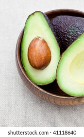 Half an avocado in an old wooden bowl