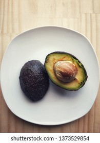 Half Avocado With Seed on White Plate and Wood Table