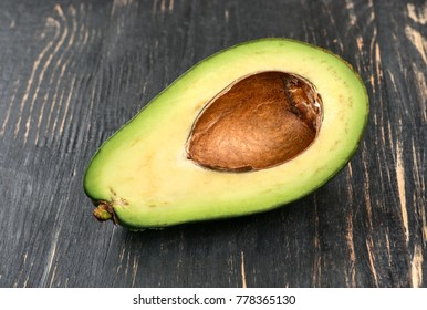 Half avocados without seeds on wooden background, closeup