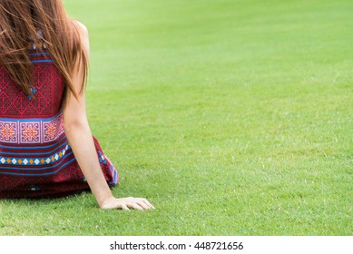 Half Back view of a young girl sitting down on green grass in the park