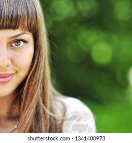 Half of beautiful girl face on nature background - copy space