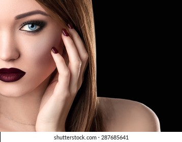 Half of Beauty Female Face. Beautiful Young Woman Model with Blue Eyes, Long Eyelashes, Dark Sexy Lips touching Cheek Isolated on Black