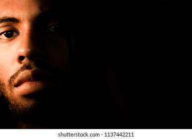 half of black mans face in shadows