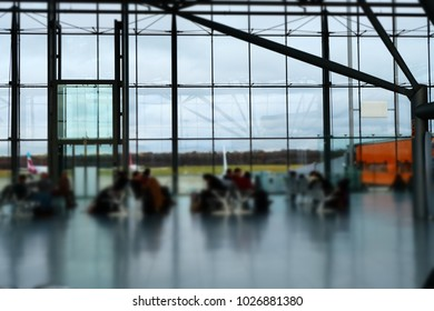 Half Blurred shot of businesspeople waiting in Airport Lobby Sitting on Chairs in Rows In front Of Panoramic Windows, Copyspace