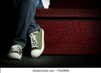 Half body of a female teenager, posing her jeans and sneakers, sitting on a red sofa.