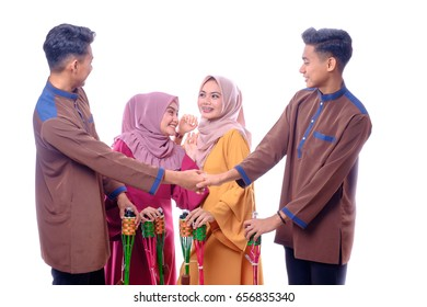 Half  body portrait of cute young twins and  beautiful women with hands holding bamboo  oil lamp standing on white background at Muadzam Shah. Eid Fitr,Happiness & Forgiveness Concept.