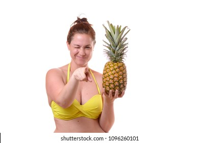Half body portrait of smiling young woman in swimsuit woman holding one pineapples and pointing to the camera