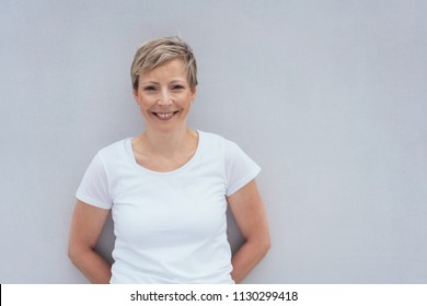Half body portrait of smiling young woman leaning against wall with copy space.
