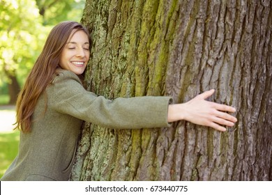 Half body portrait of smiling young woman hugging trunk of tree