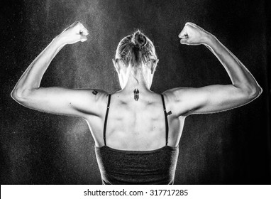 Half Body Rear View Shot of an Athletic Woman Raising her Arms Against Water Splashes in Monochrome Color.