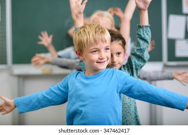 Half Body Shot of a Cute Boy Doing an Stretching Exercise inside the Classroom.
