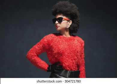Half Body Shot of a Fashionable Pretty Young Woman in Fuzzy Long Sleeved Shirt with Sunglasses Looking Into the Distance.
