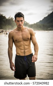 Half body shot of a handsome young man standing on a beach in Phuket Island, Thailand, shirtless wearing boxer shorts, showing muscular fit body