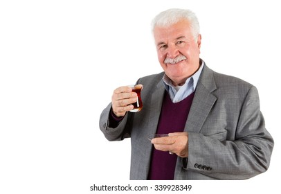 Half Body Shot of a Senior Businessman Holding a Glass of Turkish Tea and Smiling at the Camera Against White Background.