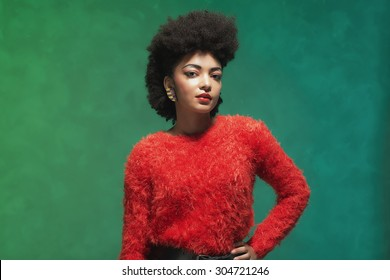 Half body Shot of a Stylish Young Woman with Afro Hair, Wearing Furry Red Shirt and Black Shorts, Looking at the Camera Against Green Wall