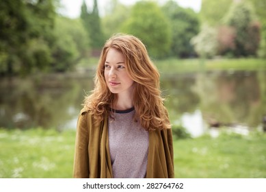 Half Body Shot of a Thoughtful Pretty Blond Girl Standing at the Lakeside While Looking Into Distance.