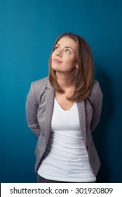 Half Body Shot of a Thoughtful Young Businesswoman Looking up While Standing Against Blue Wall Background.