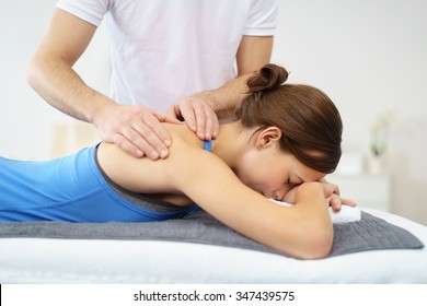 Half Body Shot of a Young Woman, Lying in Prone Position, Having a Massage on her Injured Shoulder.