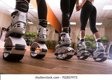 Half body of an unidentified people wearing kangoo shoes for exercises fitness. Three girls are holding hands and posed in kangoo jump shoes.
