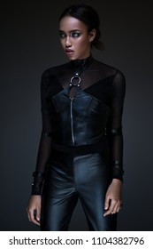 Half body view of black woman with gothic outfit posing on dark background