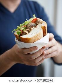 Half bread meatball sandwich on the hands on a man (Turkish street food)
