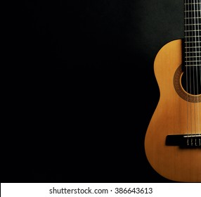 Half of a bright yellow acoustic guitar on a black background (with copy space)