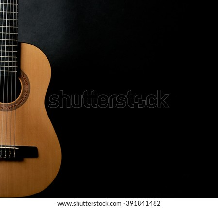 Half of a bright yellow acoustic guitar on a black background (with copy space for your text)